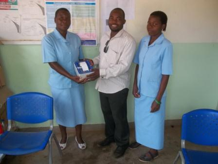 Jonathan Mtaula handing over an SMS printer to health workers